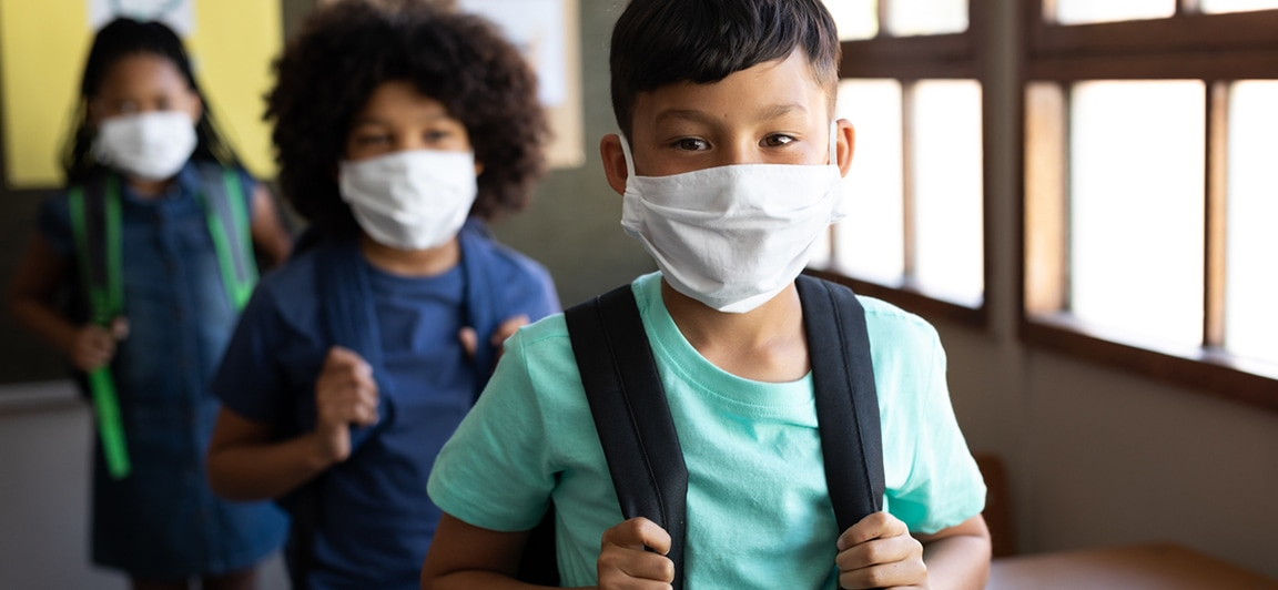 Children wearing face masks and backpacks walking down a school hallway towards the camera.