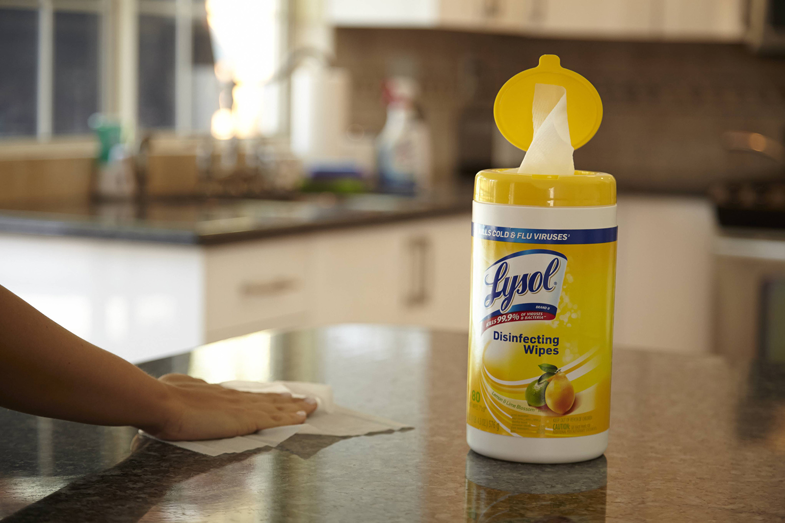 Hand wiping kitchen counted next to canister of Lysol Disinfecting Wipes