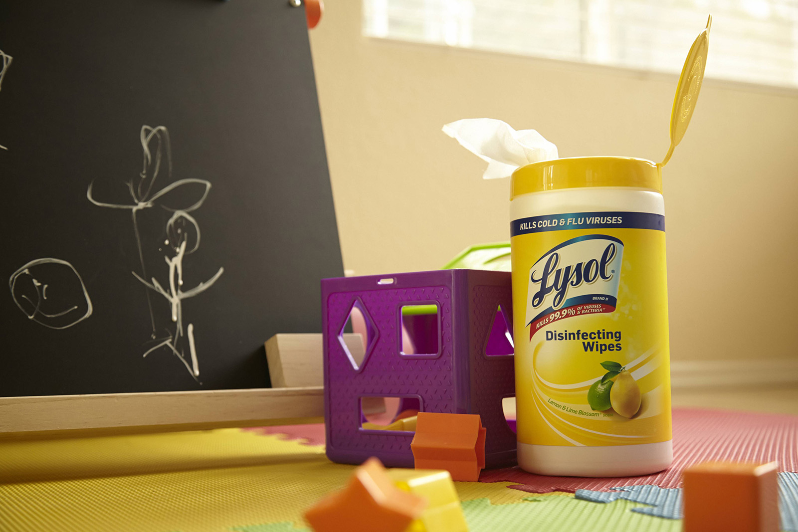 Canister of Lysol Disinfecting wipes on colorful foam floor next to toys and blackboard with chalk drawings