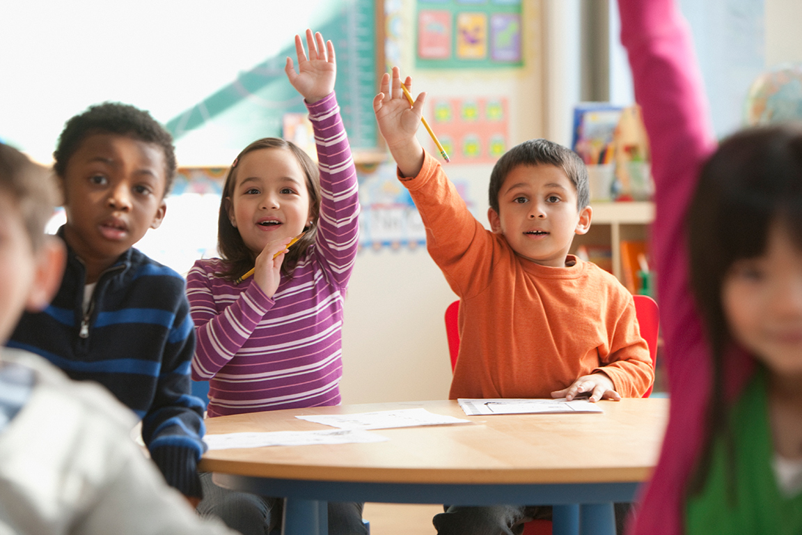 Children in classroom excitedly try to get the attention of the teacher