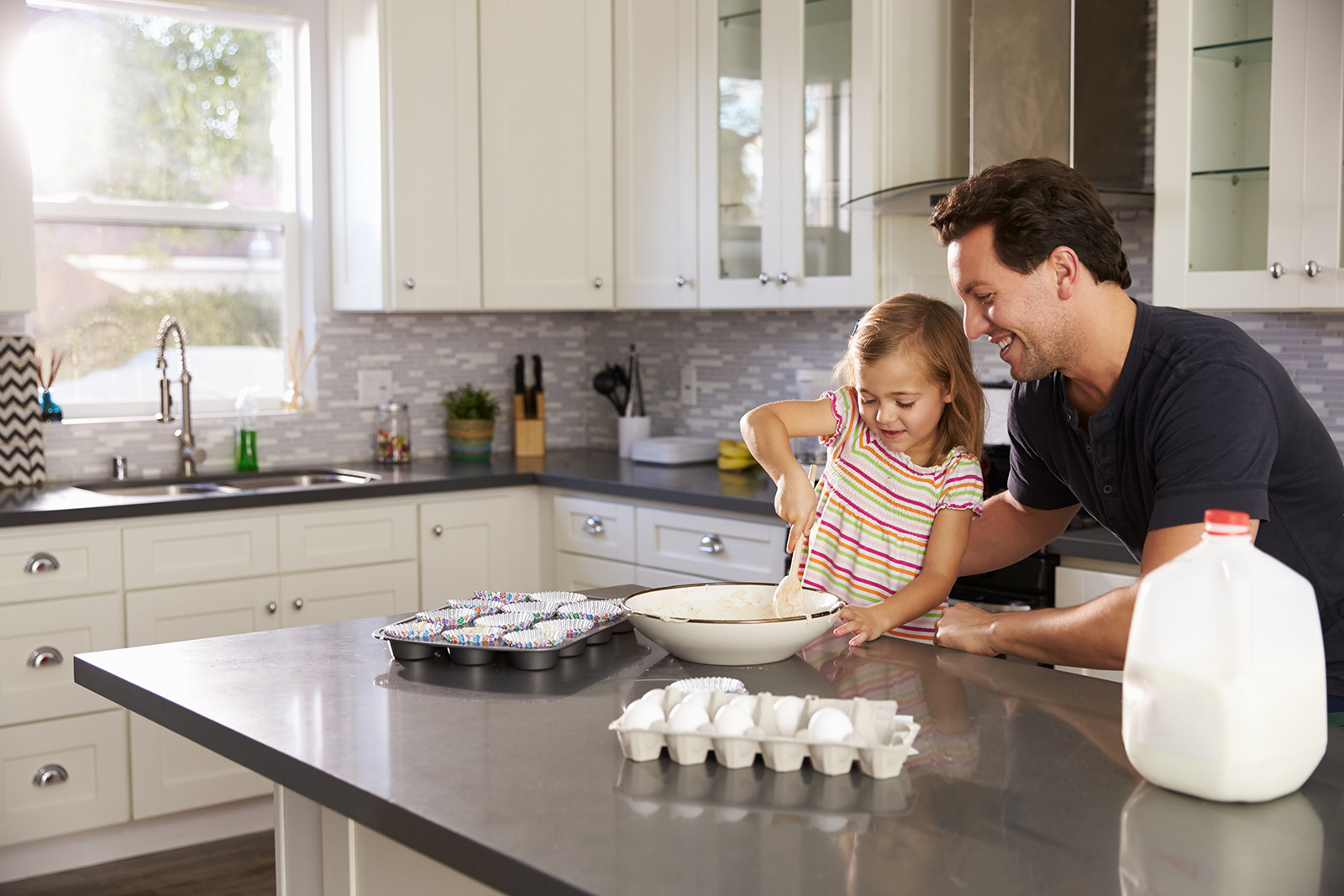 Child and parent making cupcakes on a kitchen counter
