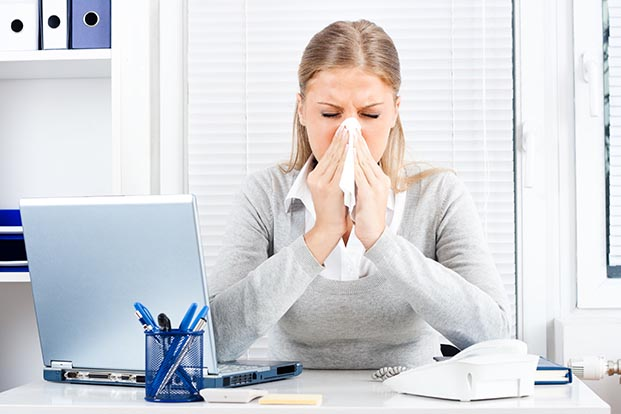 Person in office in front of laptop blows nose into tissue