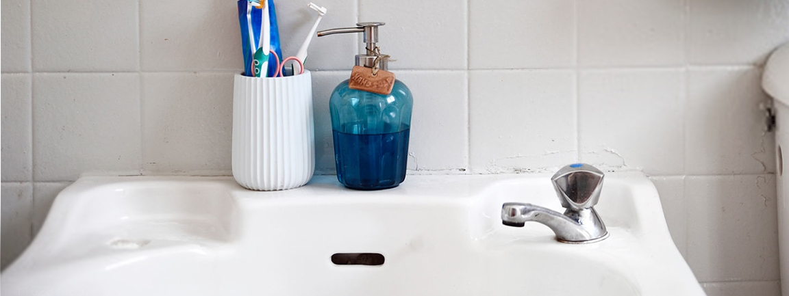 Bathroom sink with liquid soap and toothbrushes