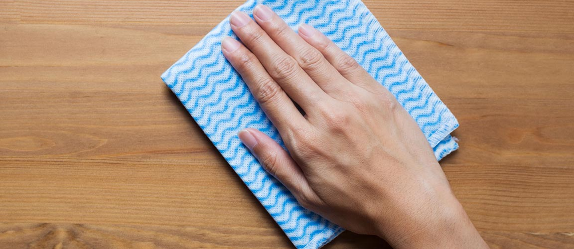 Hand wiping cloth over hard wood surface