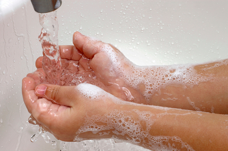Childs hands covered with soap foam under running faucet