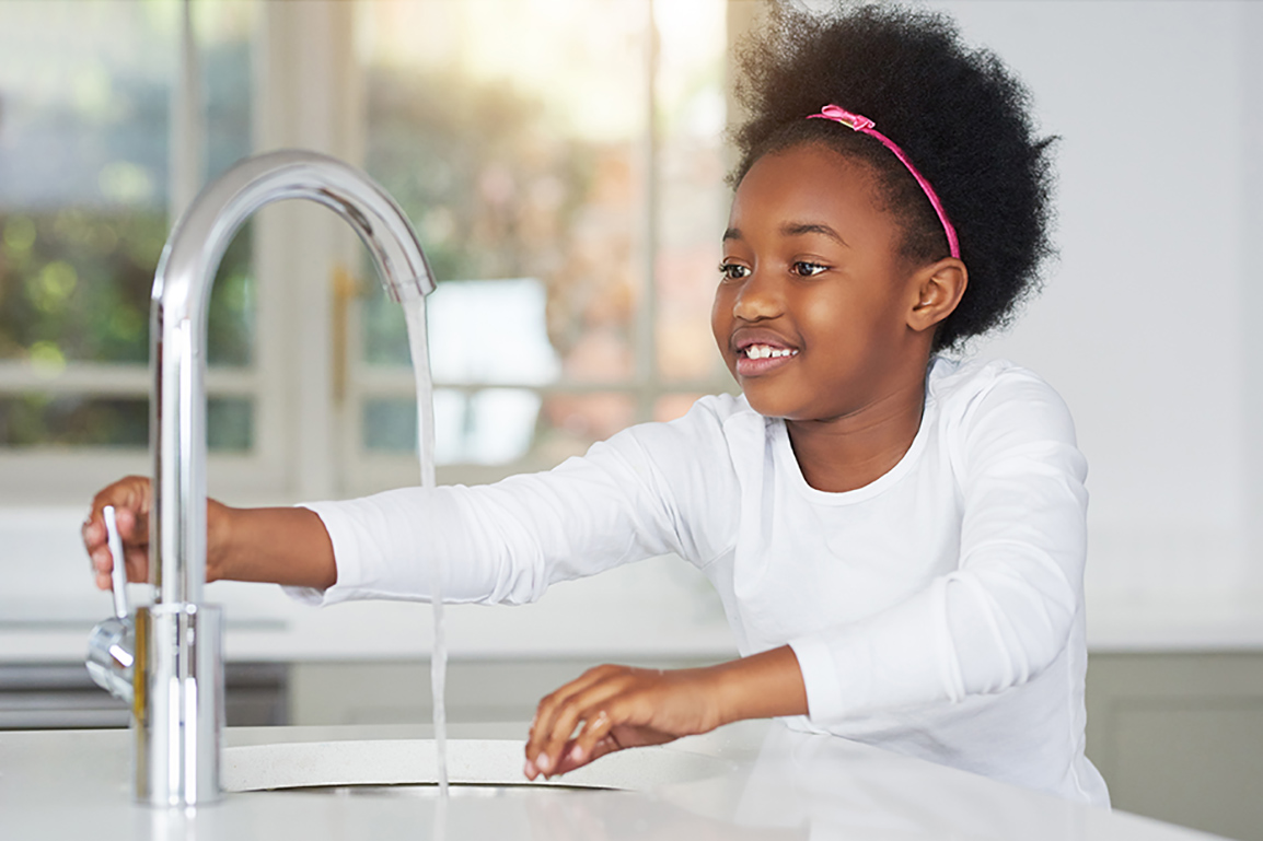 Child turning on faucet