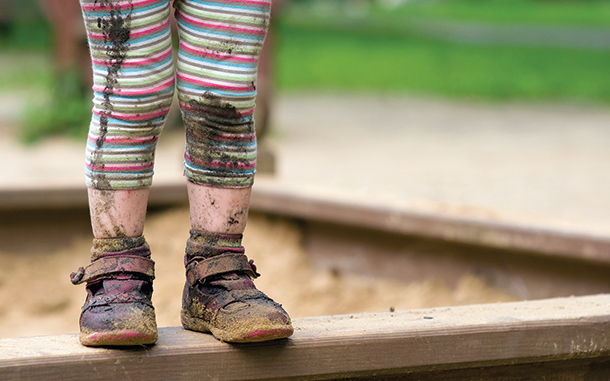 Legs and feet of muddy child in sand pit