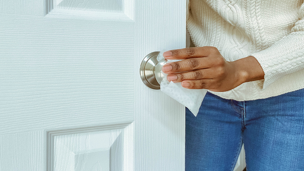Person wiping the chrome doorknob of a white door