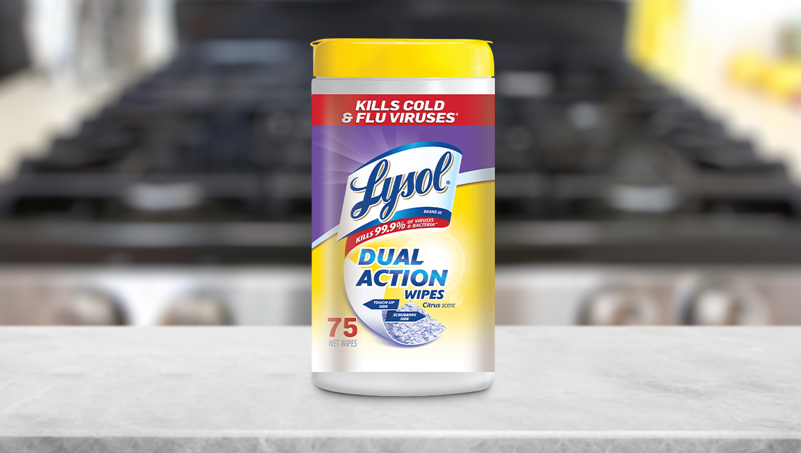 A canister of Lysol Dual Action Disinfecting Wipes resting on a kitchen counter. An oven is in the background.