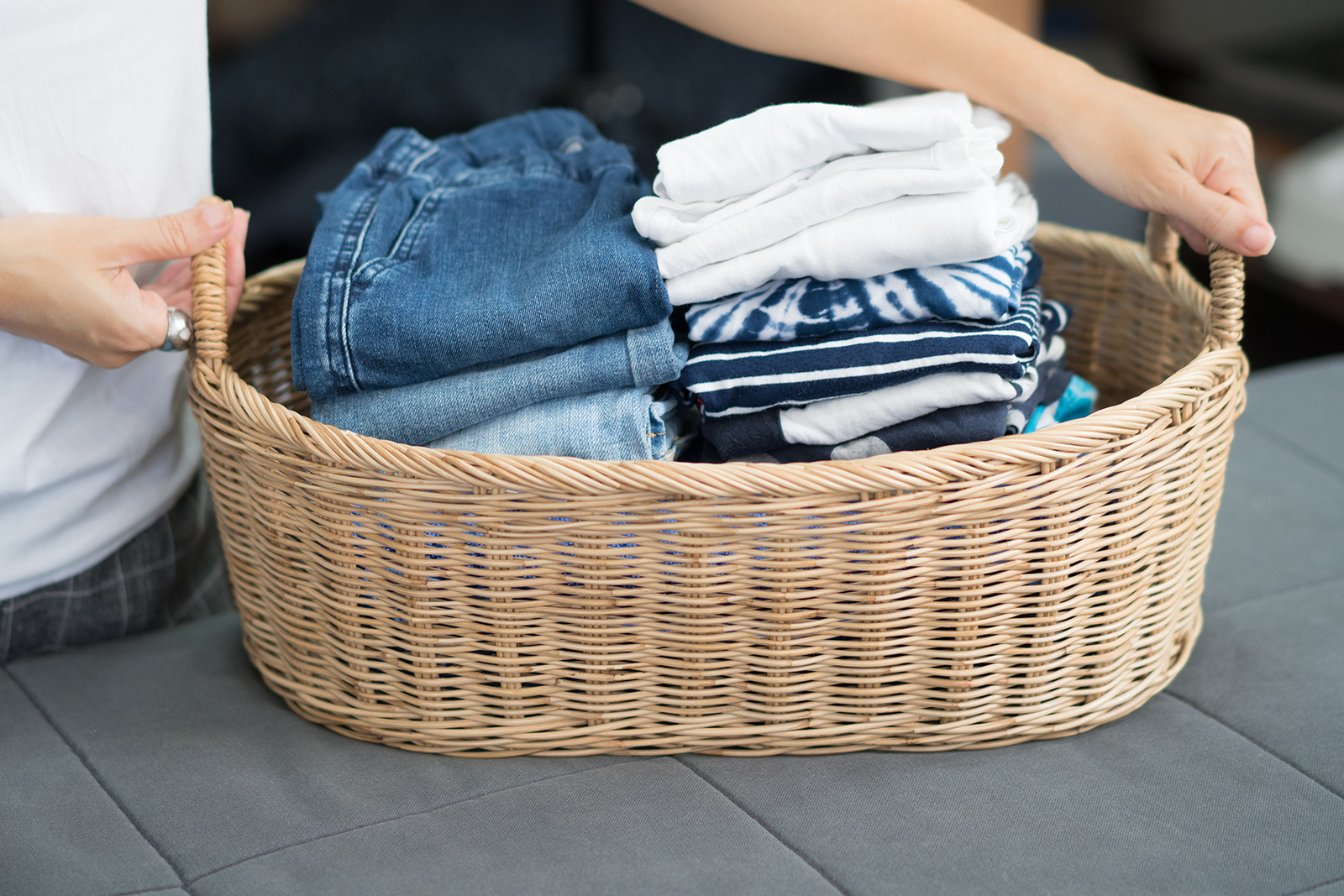 Person holding handles of straw laundry basket with neatly stacked clothes inside
