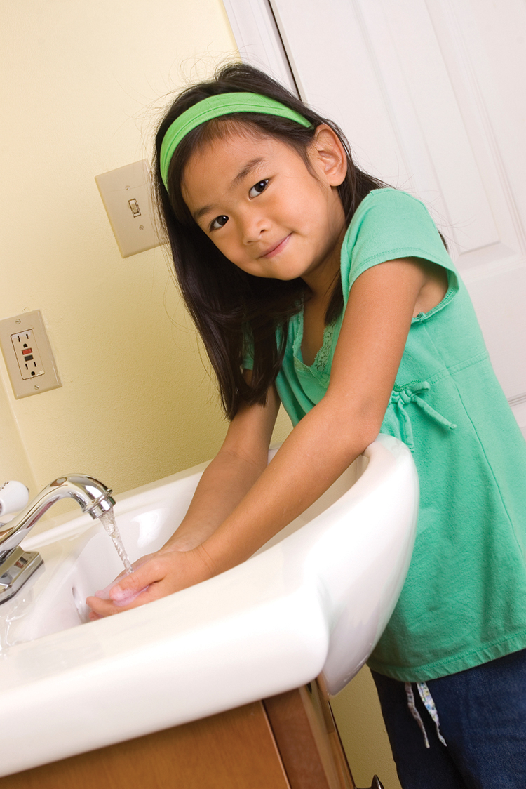 Child leans over bathroom sink with running faucet