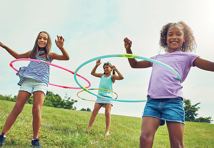Three children stood in grass field spinning colorful hula hoops on their waists