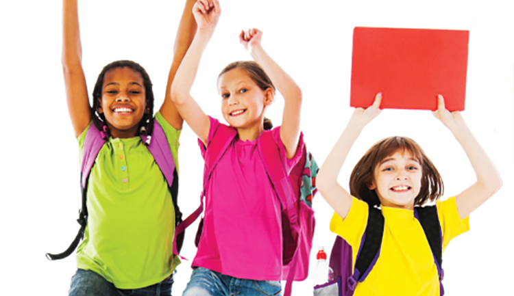 Children with backpacks holding hands and workbooks in the air and jumping