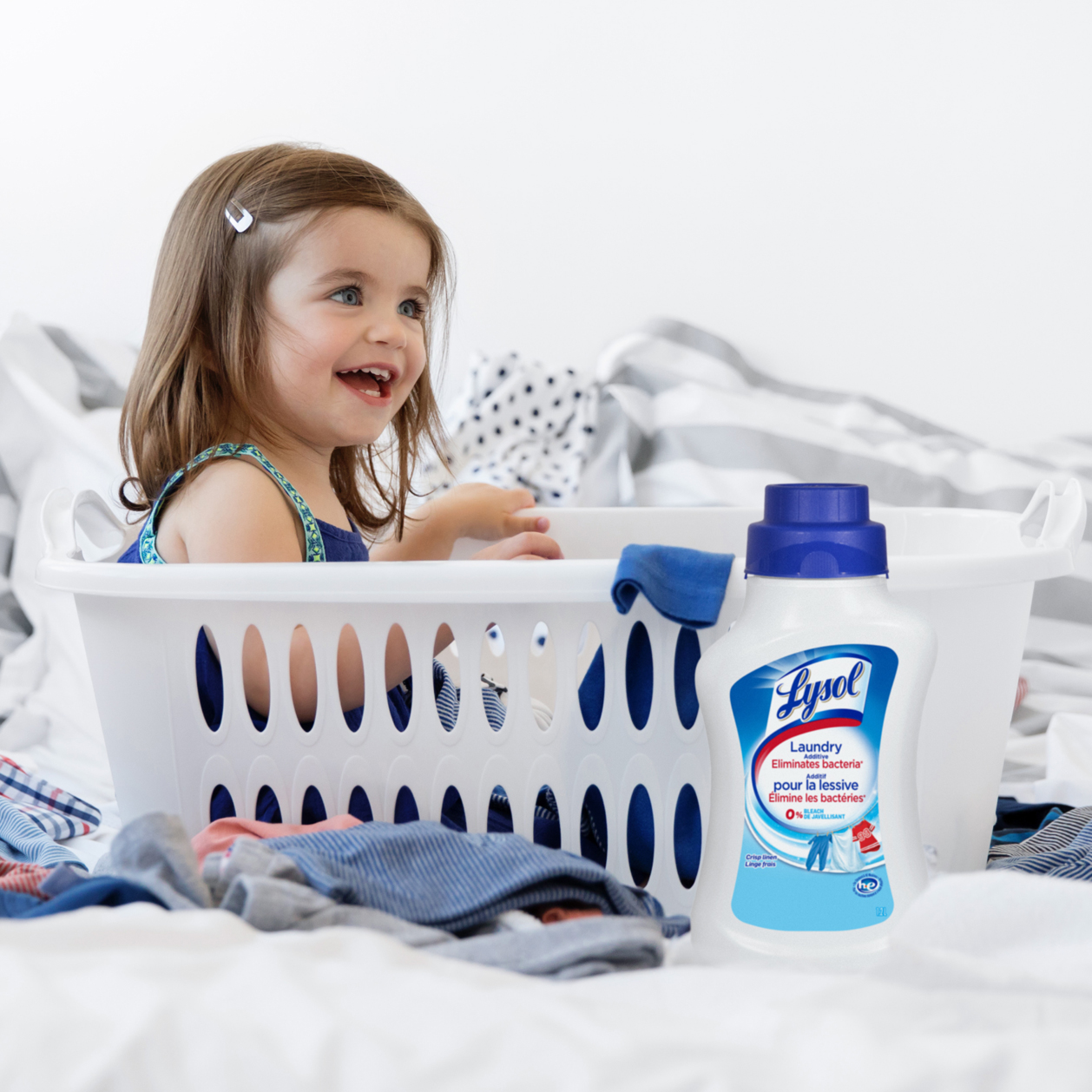 Young child sitting in plastic laundry basket and smiling surrounded by laundry and container of Lysol Laundry Sanitizer