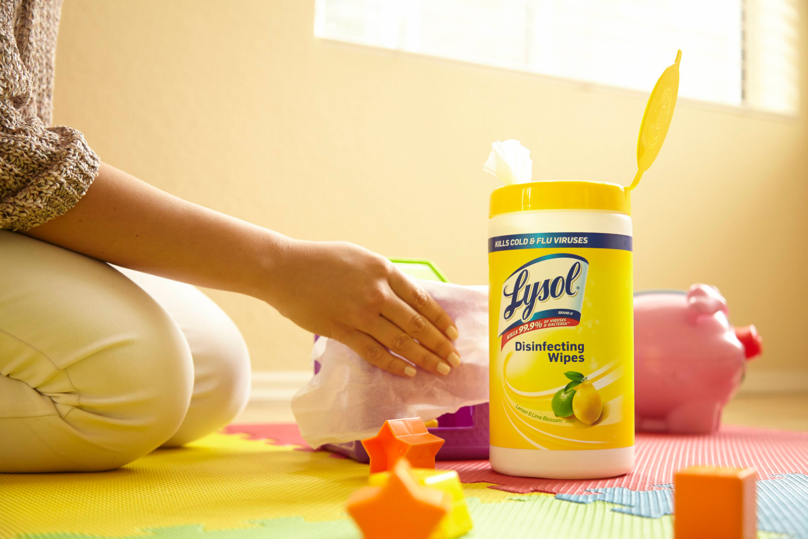 Parent kneeling on floor and wiping baby toys next to canister of Lysol Disinfectant wipes