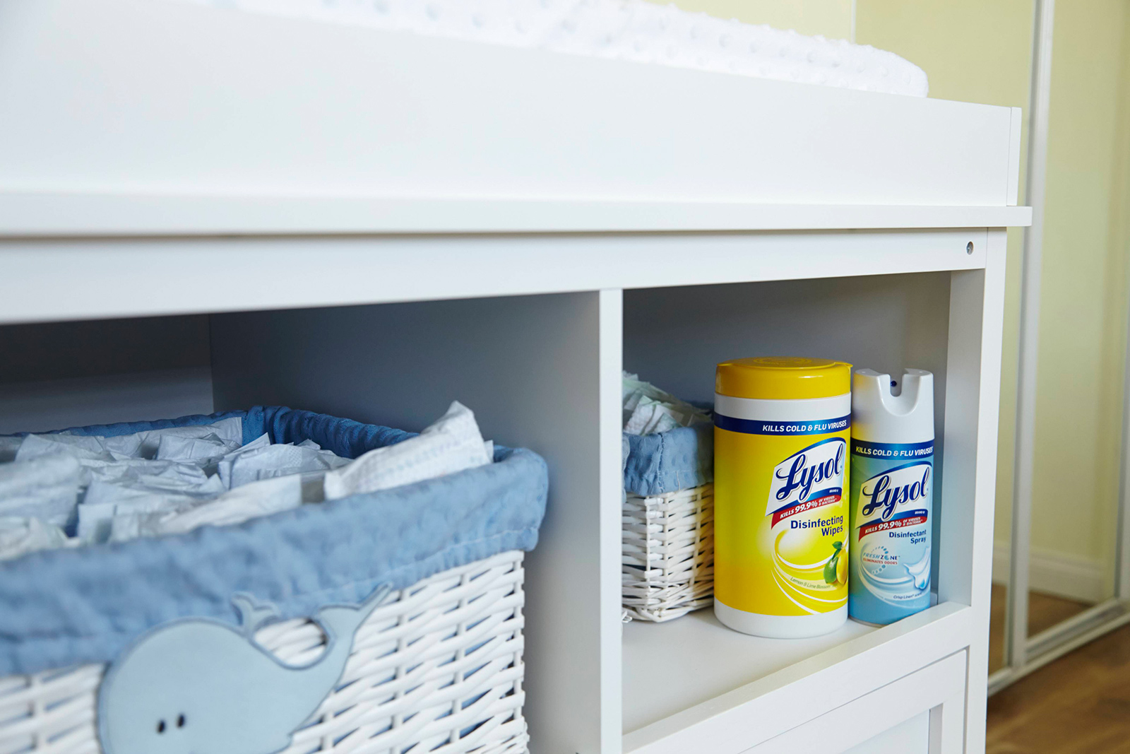 Cabinet with baskets containing diapers and canisters of Lysol Disinfecting Wipes and Lysol Disinfectant Spray