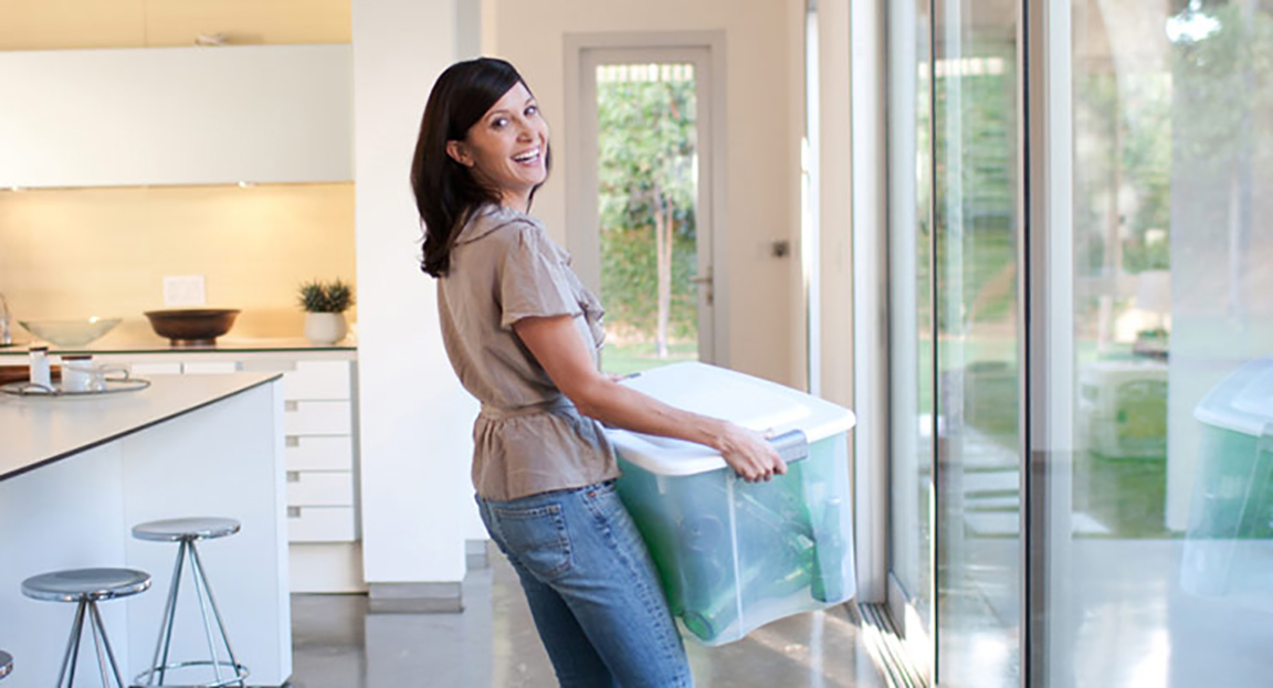 Adult carrying large plastic storage box inside home