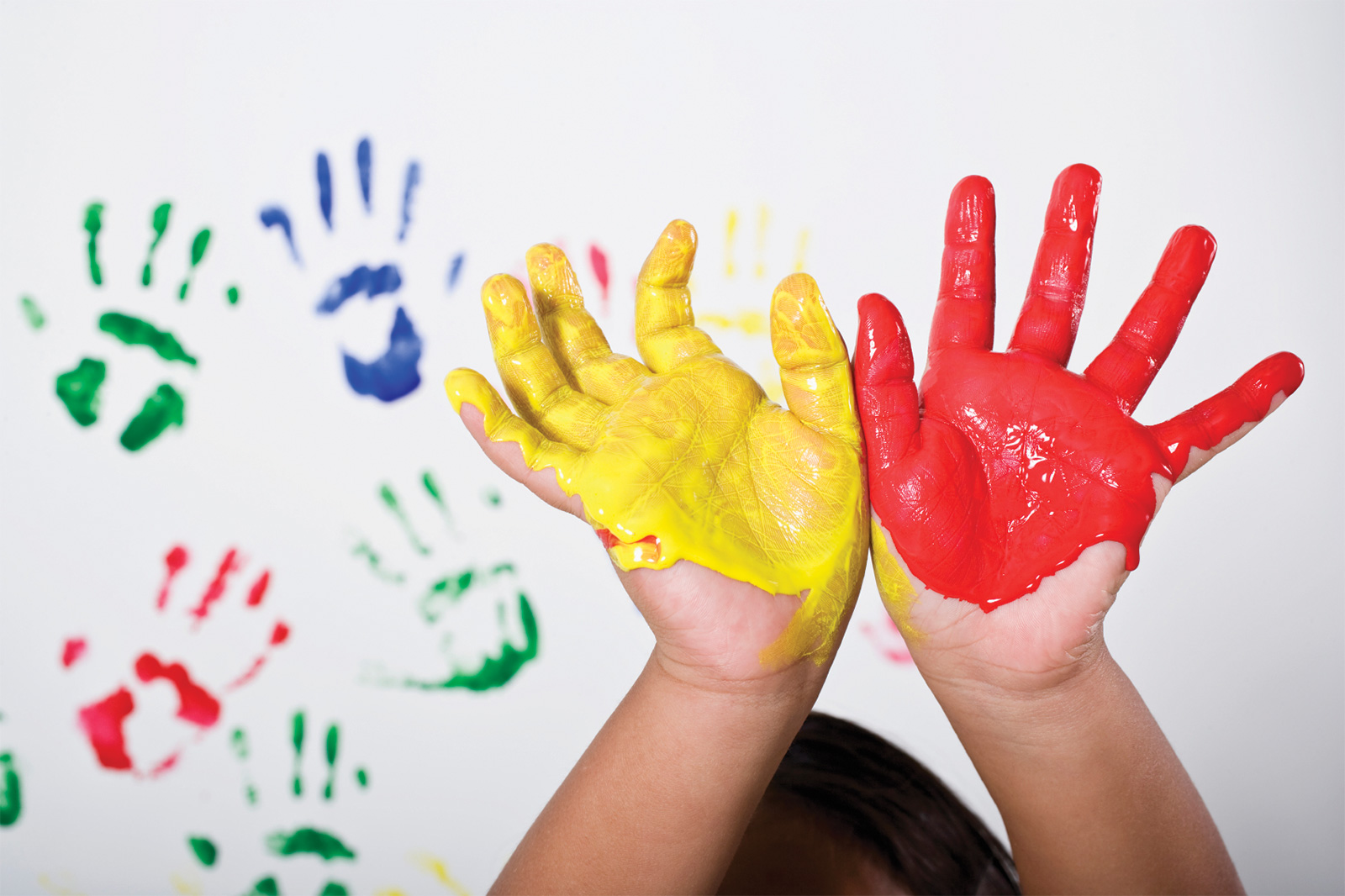 Hands of child covered in paint in front of white surface with paint handprints
