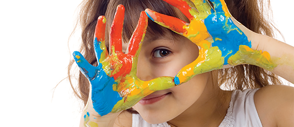 Child holding paint covered hands up to their face