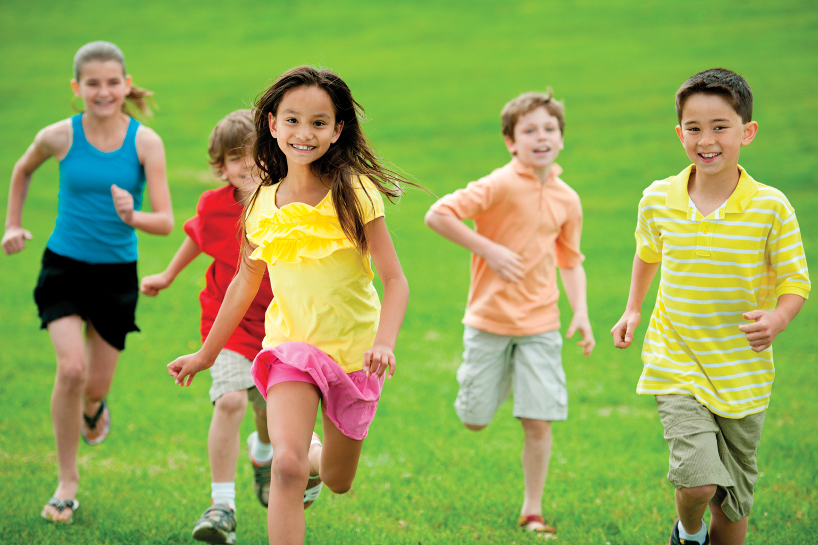 Children in bright clothing running on green grass field