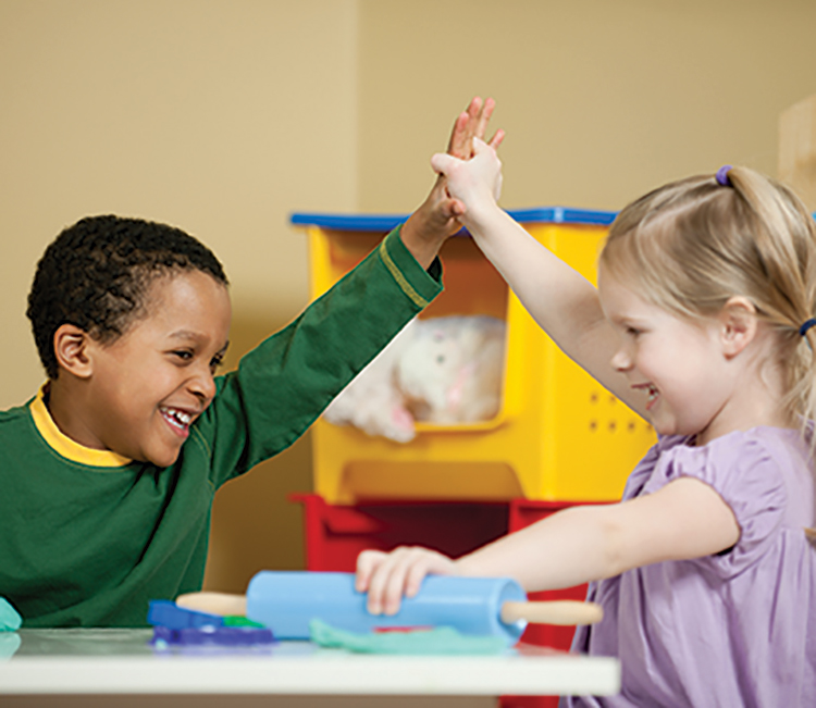 Children holding hands and rolling out salt dough