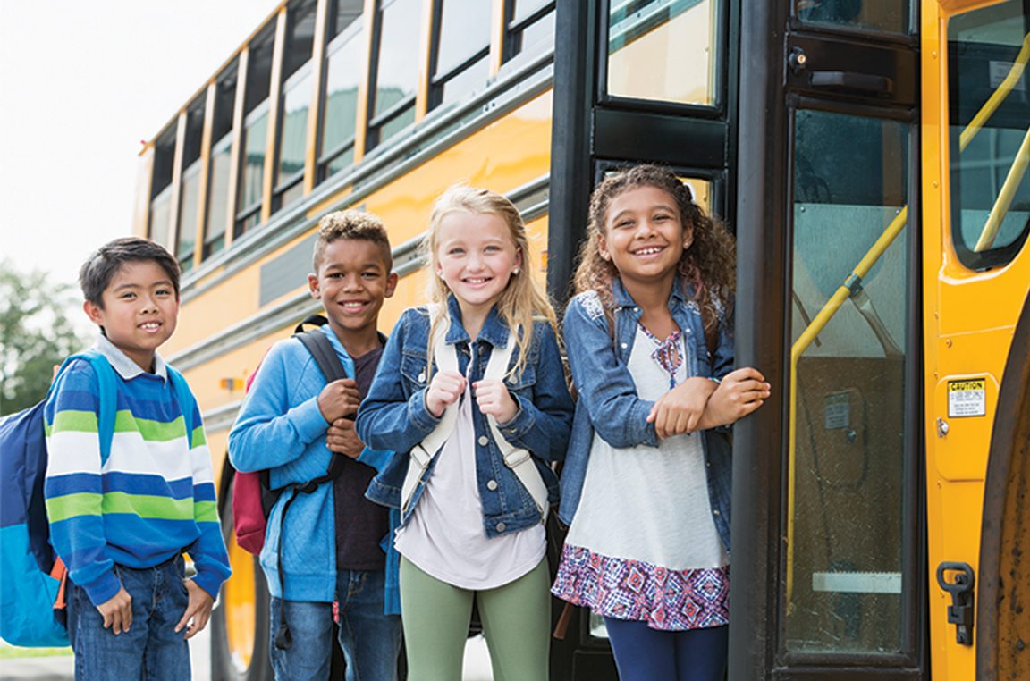3 children with jackets and backpacks smiling in front of school bus door