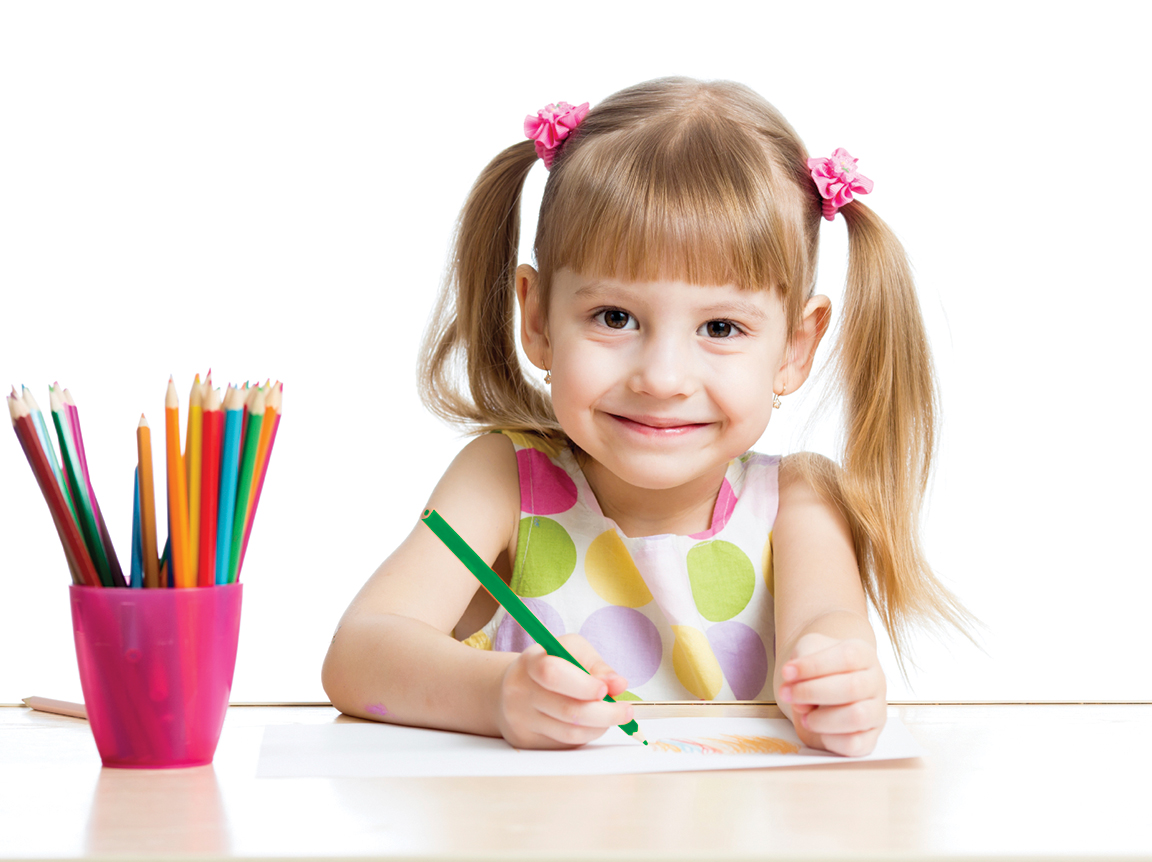 Child next to pot of pencils smiling at camera and drawing on paper