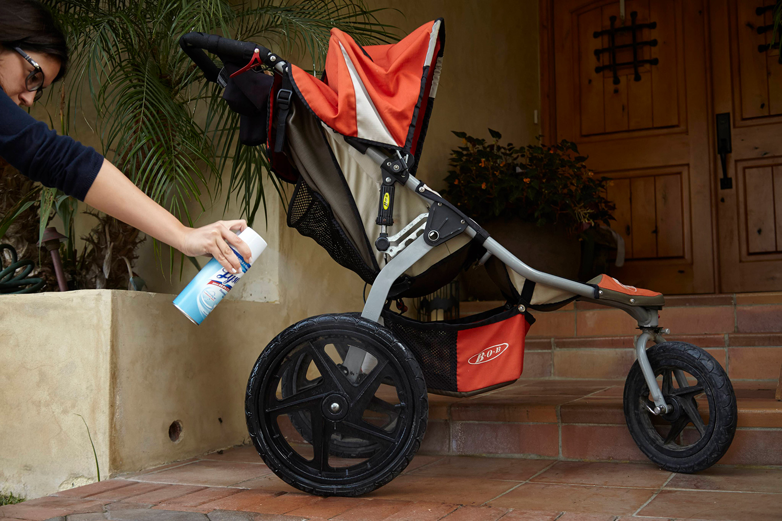Person spraying the wheels of a stroller with Lysol Disinfectant Spray