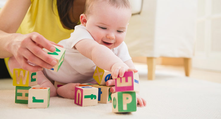 Parent helps baby build stack of lettered blocks when sitting on floor