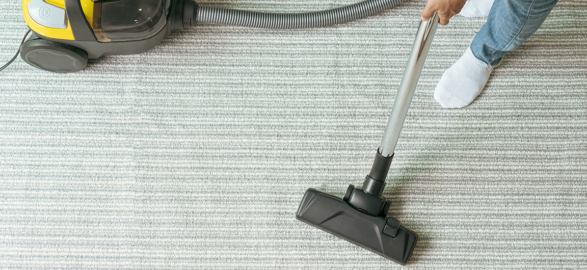 A vacuum being used on a living room carpet.