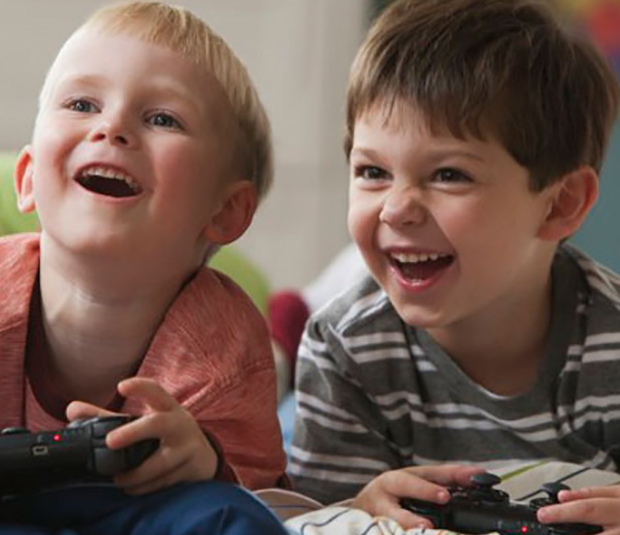 Children lying on bed holding gaming console controller and laughing