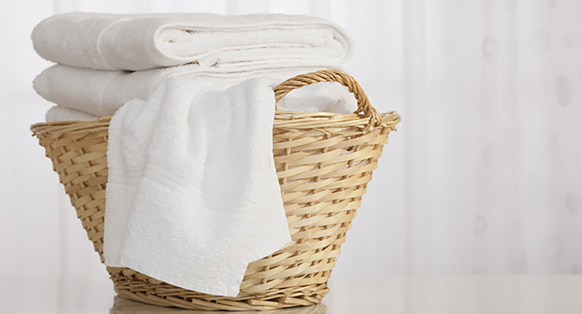 Straw laundry basked filled with clean white towels