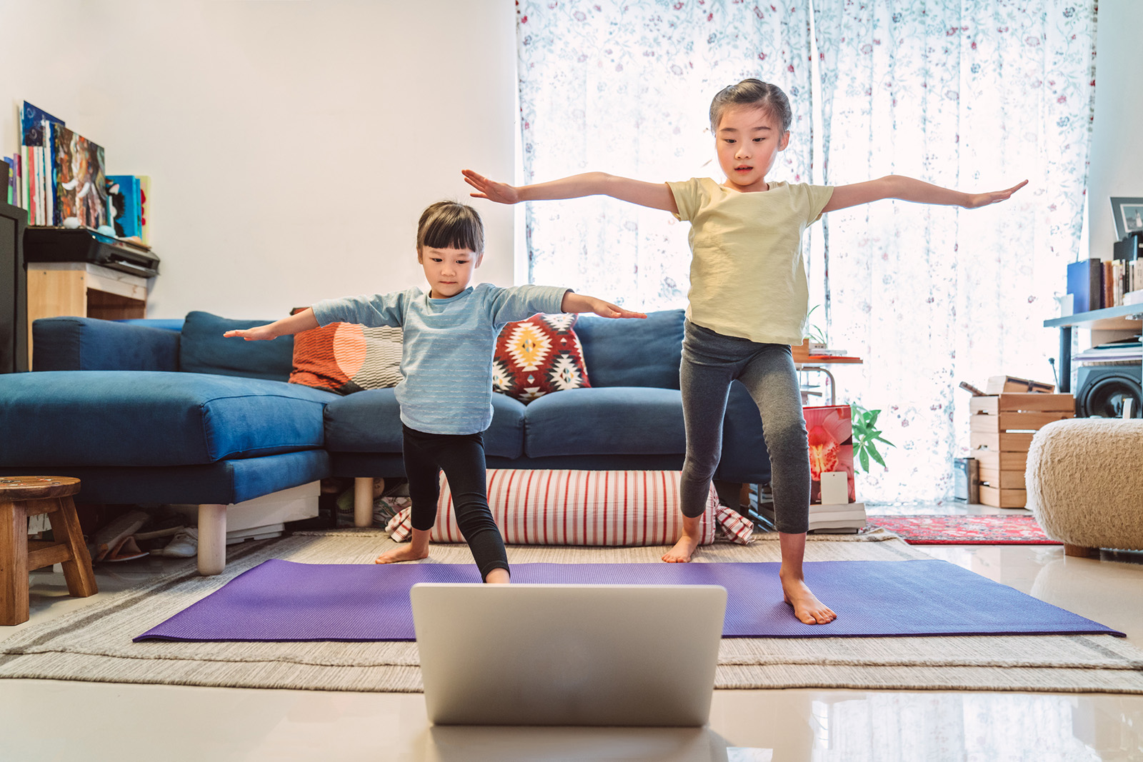 Two children doing yoga pose while standing on yoga mat in living room and looking at laptop screen