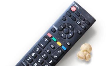 Black remote control next to a piece of popcorn