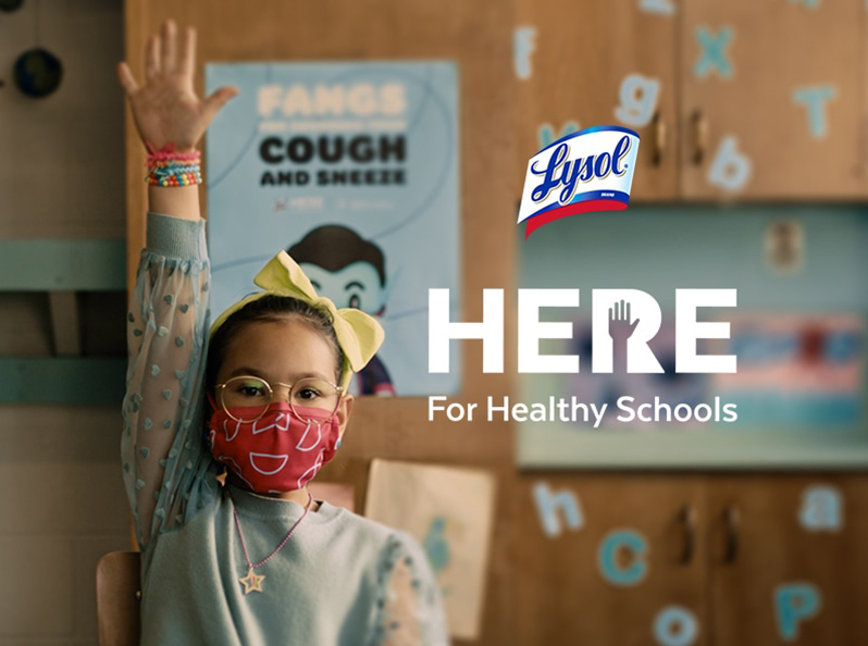 "A student wearing a face mask raises their arm to attract the attention of a teacher. The CDC Foundation ""Cover coughs and Sneezes"" poster is in the background and the Lysol Here for Healthy Schools logo overlays the image."
