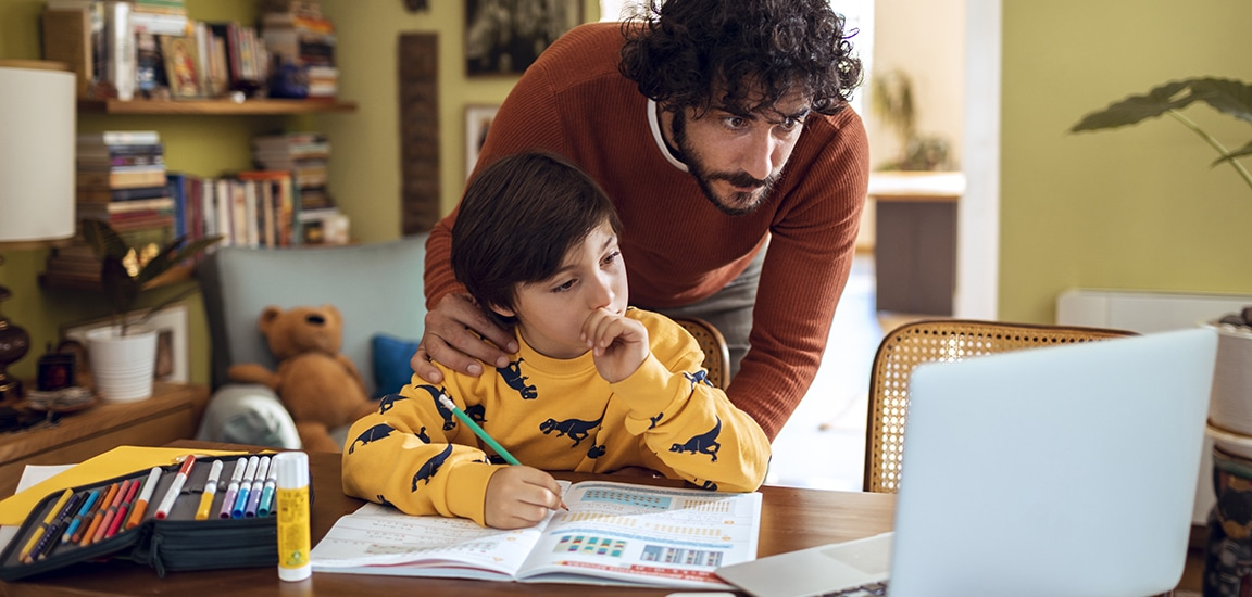 Close up of a father helping his son with schoolwork in their home
