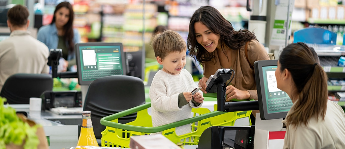 Parent showing child how to insert credit card into card reader at grocery store checkout. The Cashier is smiling at them