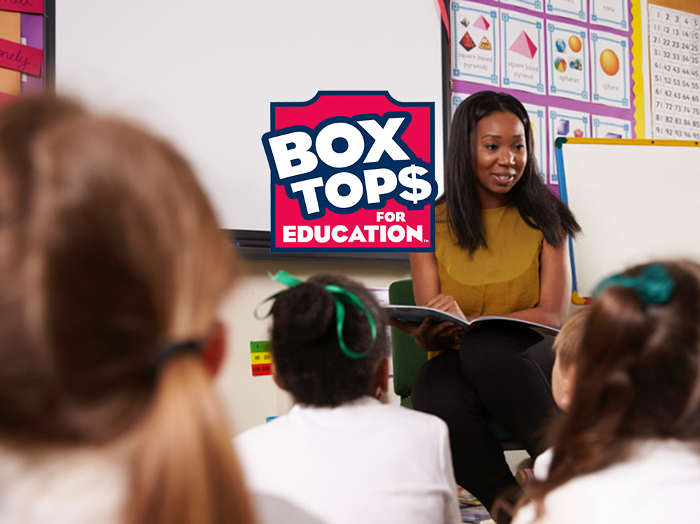 A teacher at the front of a classroom reading a book to a group of elementary students. Box Tops for Education Logo overlays the image.