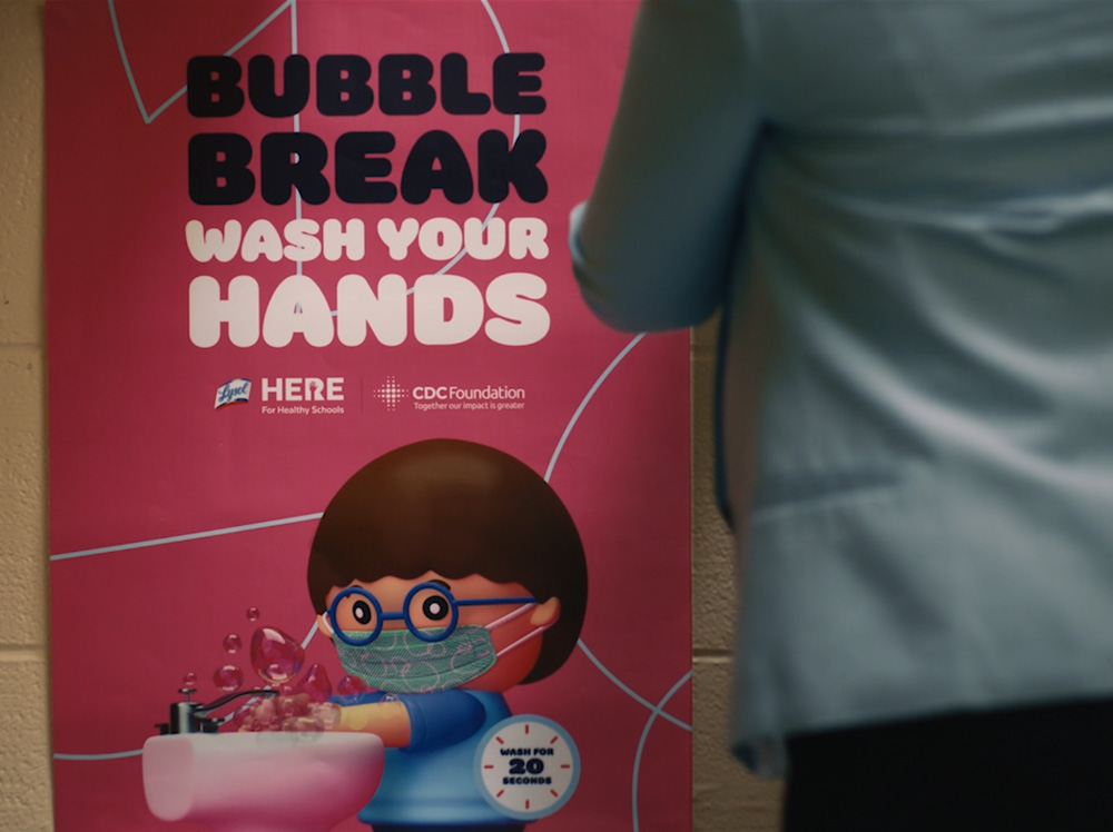 "A teacher stood in front of the CDC foundation ""Bubble break wash your hands"" poster."