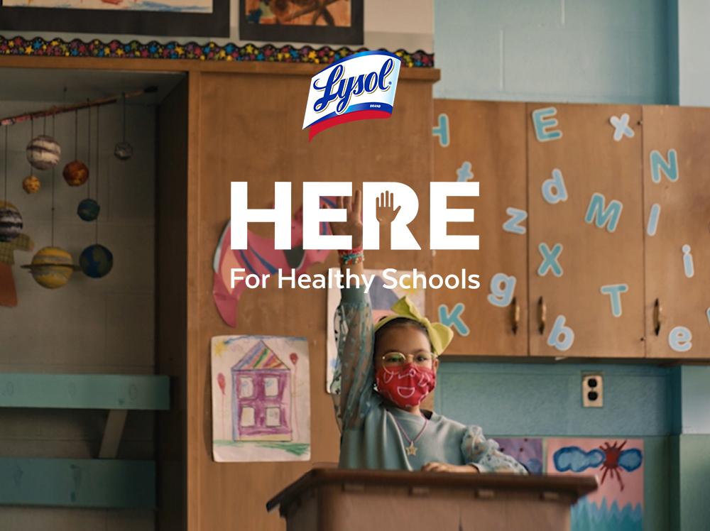 A student wearing a face mask in a classroom raises their hand to attract the attention of the teacher. The Lysol Here for Healthy Schools Logo overlays the image.