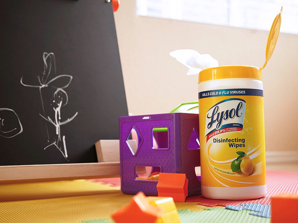 A canister of Lysol Disinfecting Wipes on the floor of a playroom next to a chalkboard and some baby toys.