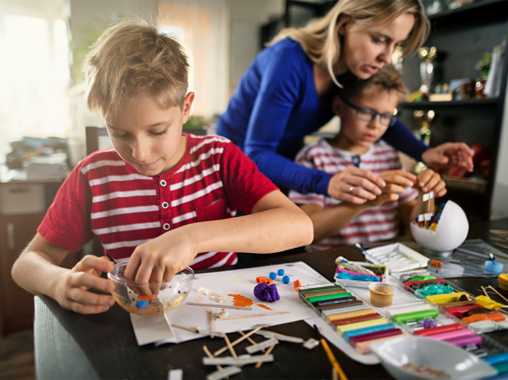 A parent helping their children create with arts and crafts.