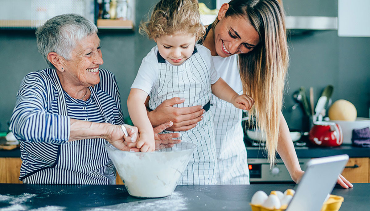Happy grandmother, daughter and granddaughter having fun while making a dough