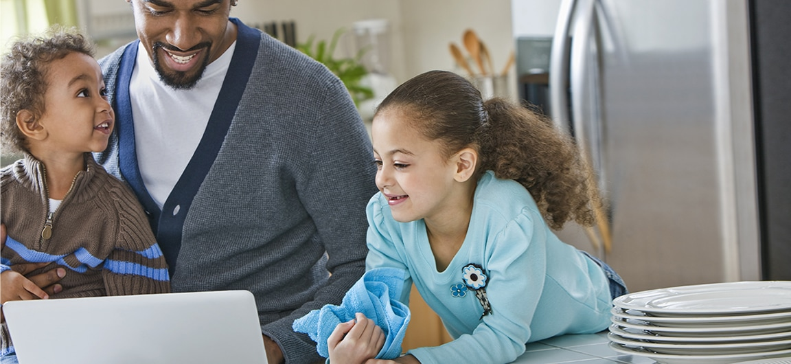 A parent and two children in a kitchen. The parent is showing the children something on a laptop computer. One of the children has a drying cloth in their hand and is next to clean and dry dishes.