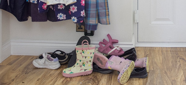 A front entry way of a house with shoes and boots laying by the door and coats hanging above
