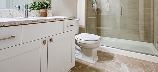 A bathroom featuring a sink vanity, toilet and shower.