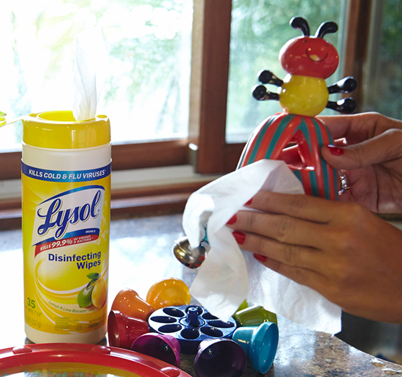 Hands using Lysol Disinfecting Wipes to clean and disinfect baby toys.