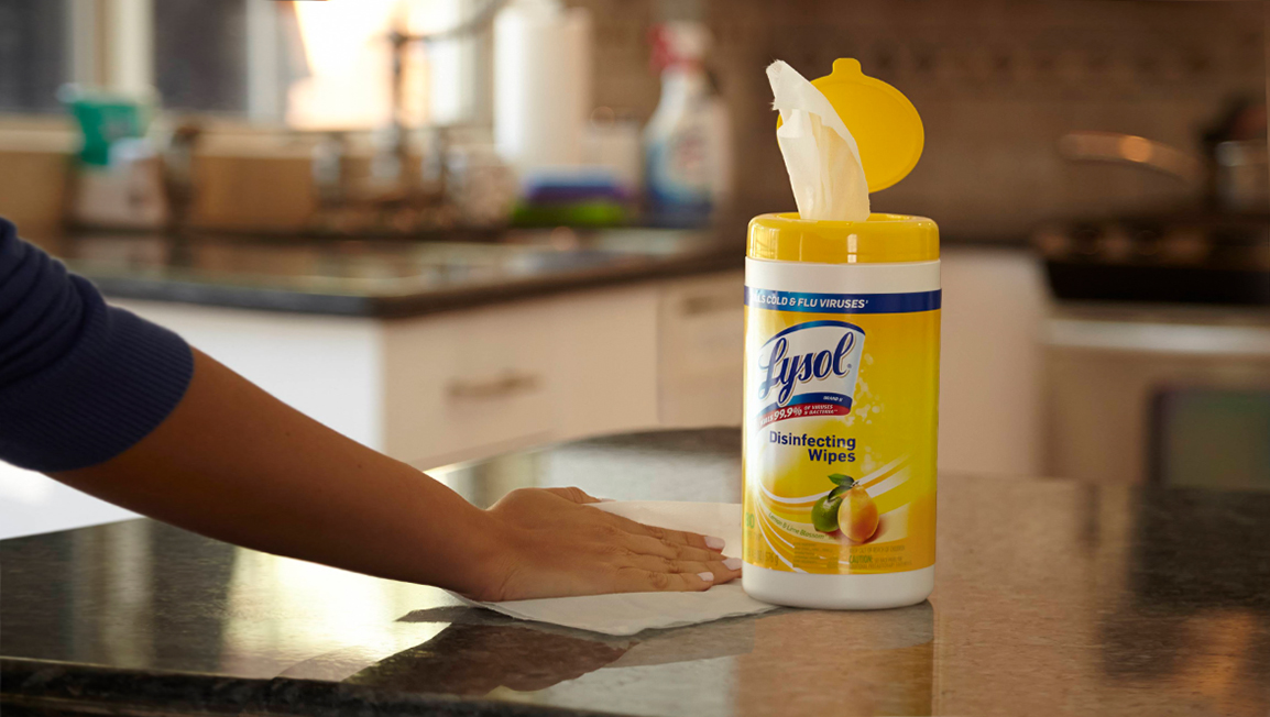 A canister of Lysol Disinfecting wipes on a kitchen counter. A hand is using a wipe to wipe down the counter next to the container.
