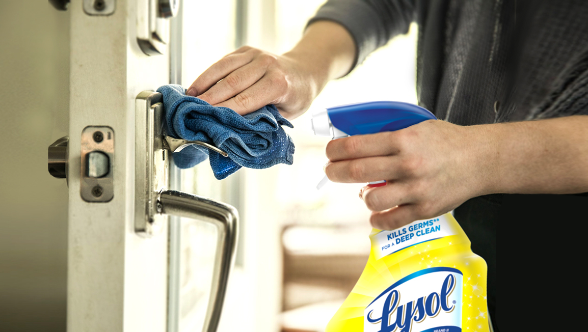 A bottle of Lysol Multi-Purpose cleaner and a cloth being used to clean a door latch.